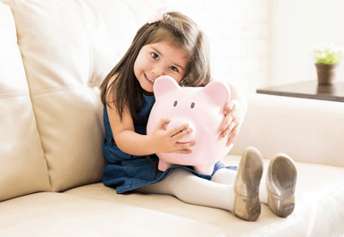 little girl smiling holding piggy bank