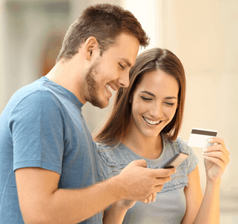 Couple looking at credit card and phone