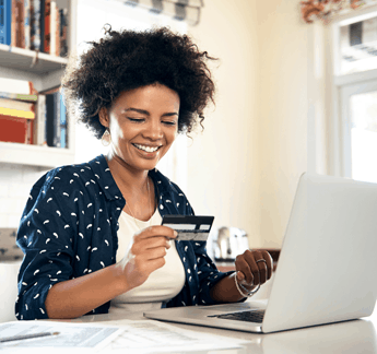 woman looking at her credit card and computer